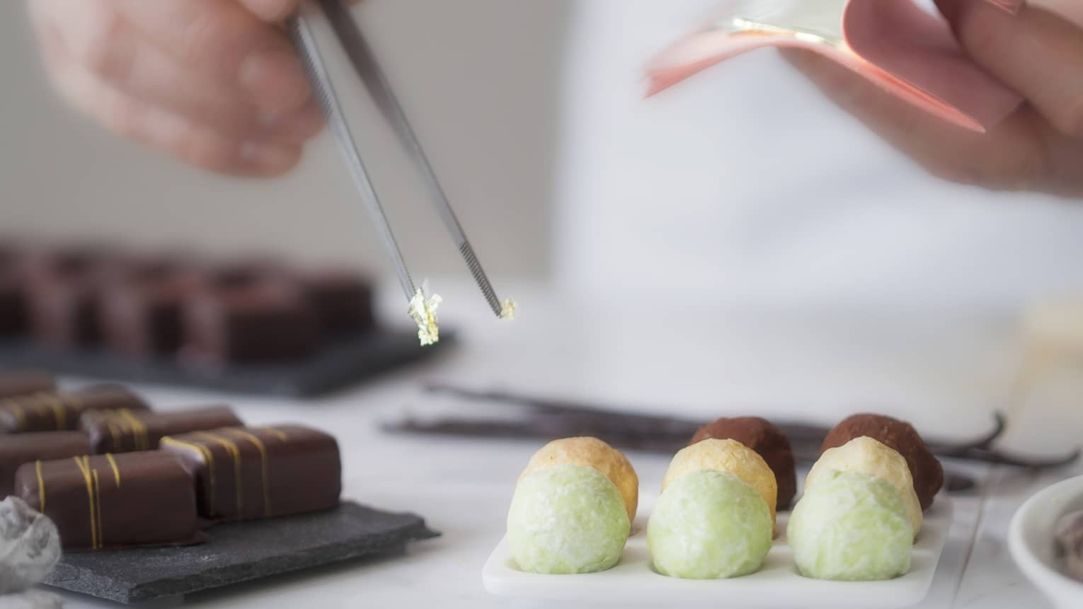 A close up of a male chef's hands using tongs to place various chocolates on parchment paper
