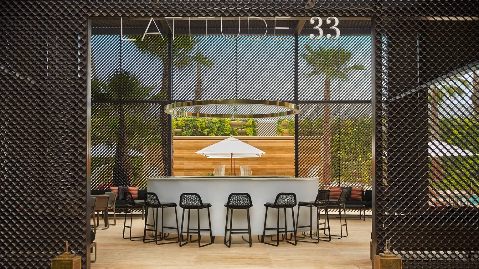 Latitude 33 bar entrance, white bar with black bar chairs, palm trees outside