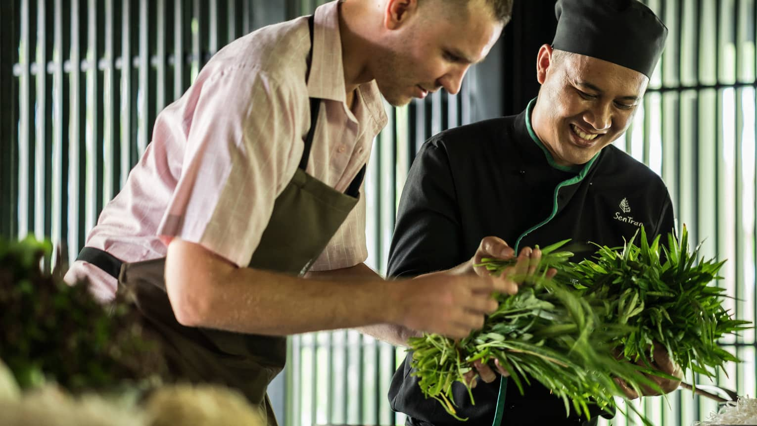Smiling Chef Tran Van Sen holds greens, shows them to man in apron