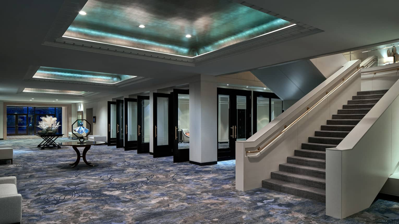 Events hall with blue-ish carpeting, grand staircase and inset metallic ceiling with recessed lights