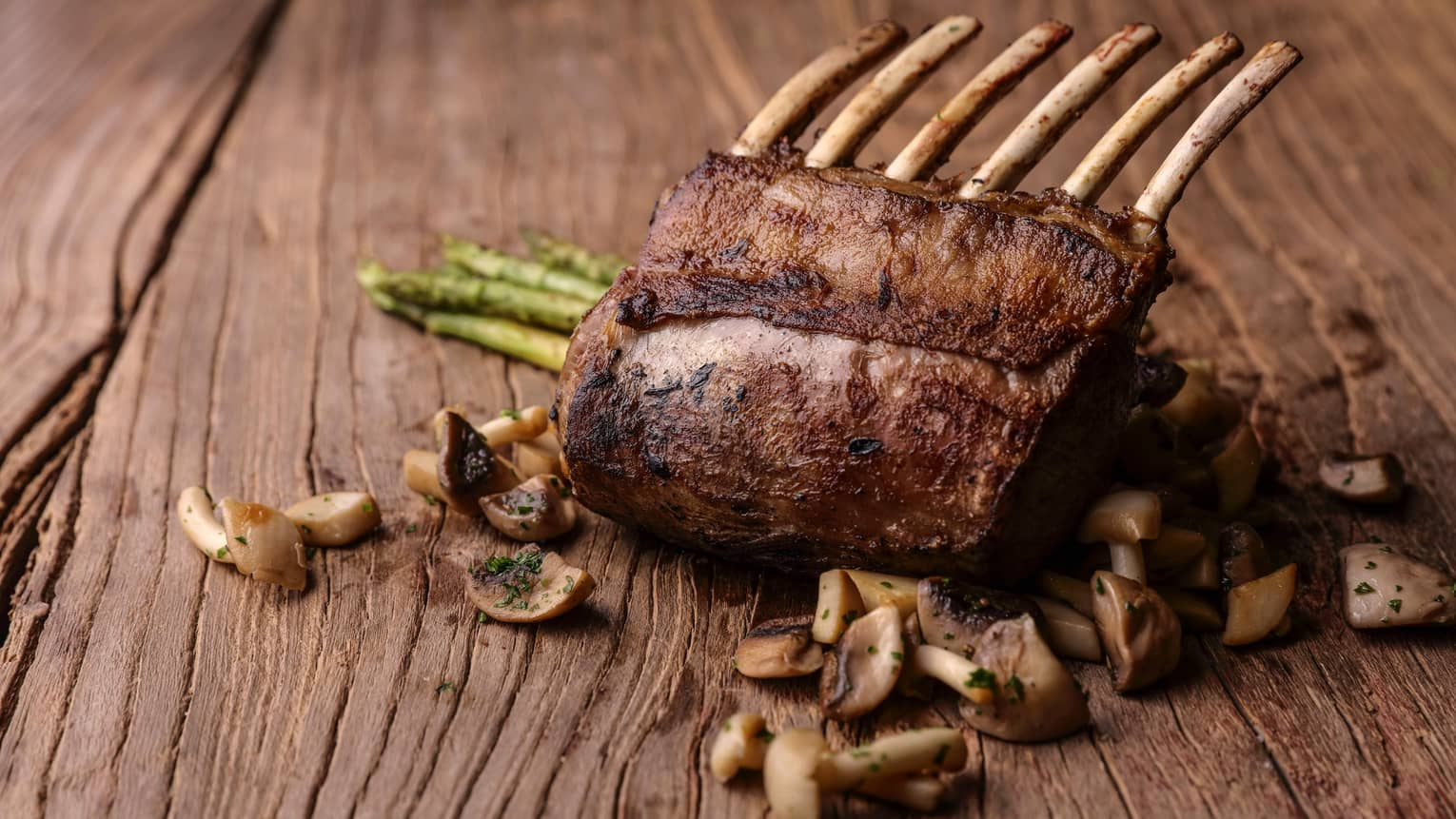 Grilled Australian Lamb rack on wood counter with mushrooms, asparagus
