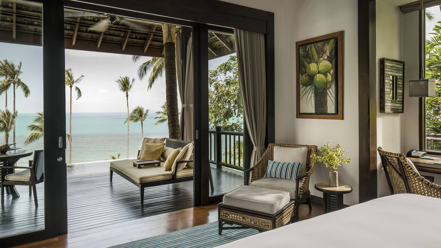 Villa bedroom with queen bed, rattan furniture and private beach access