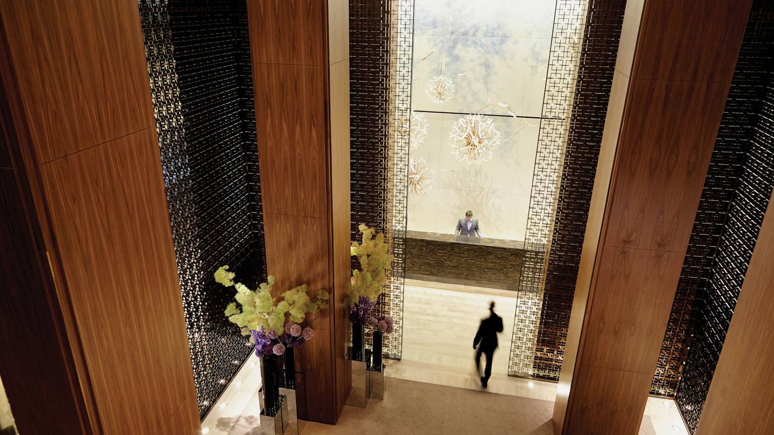 Aerial view of long wood pillars, flowers in dimly-lit lobby, man in suit walking towards reception