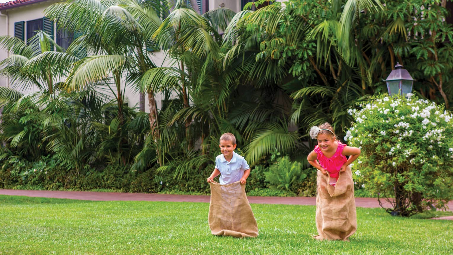 Two smiling children race across lawn in burlap sacks