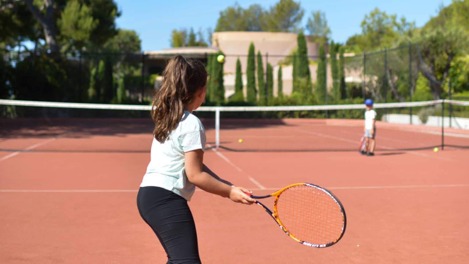 Girl with brown ponytail in light blue T-shirt and black pants playing tennis on clay court
