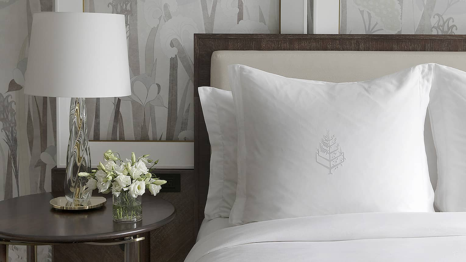 White flowers decorate a bedside table next to a bed with crisp, white sheets