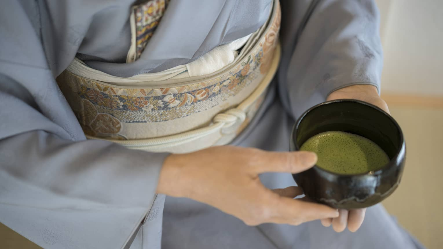Close-up of woman in blue robe holding bowl with green matcha tea