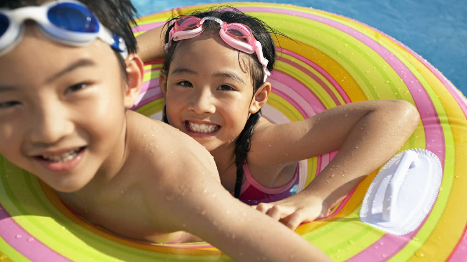 Smiling brother and sister with goggles on head share inflatable tube in swimming pool
