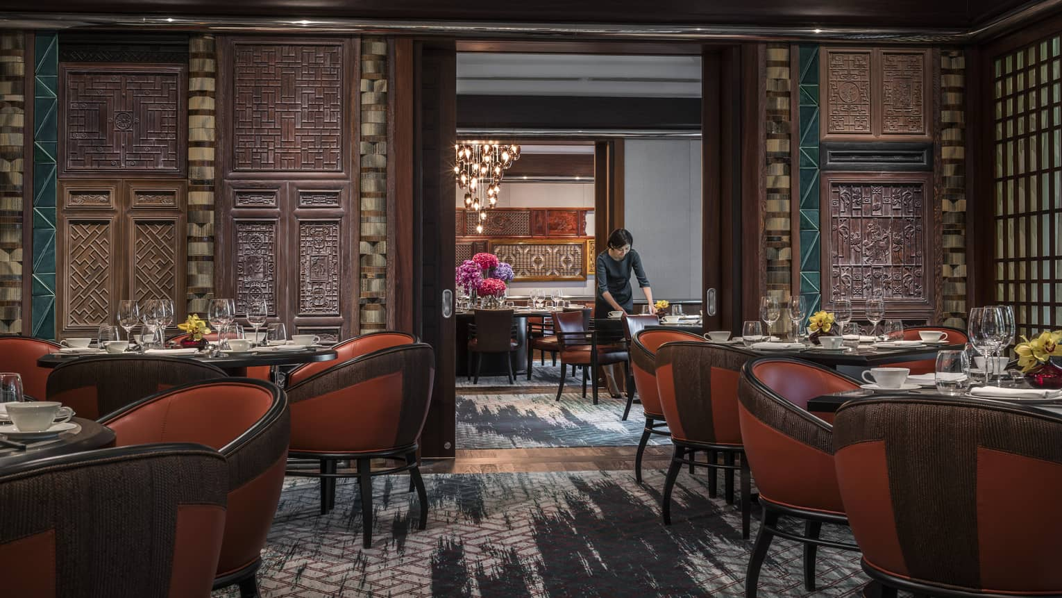 Woman sets table at Jiang-Nan Chun, Michelin-starred Cantonese restaurant, with red leather bucket chairs around dining tables, carved wood walls.