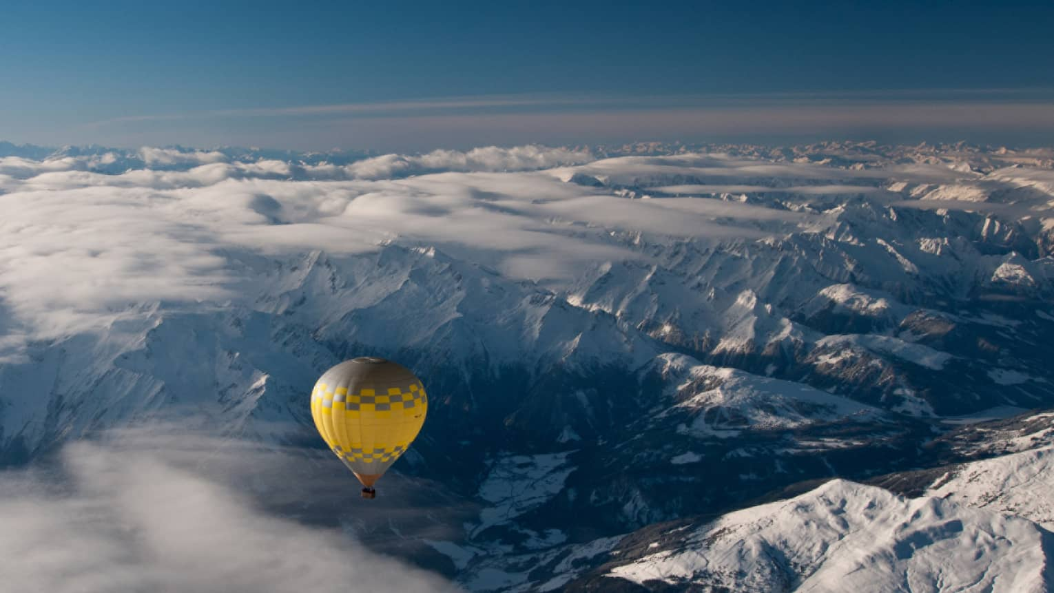 Yellow hot air balloon soaring over the snow-covered Alps