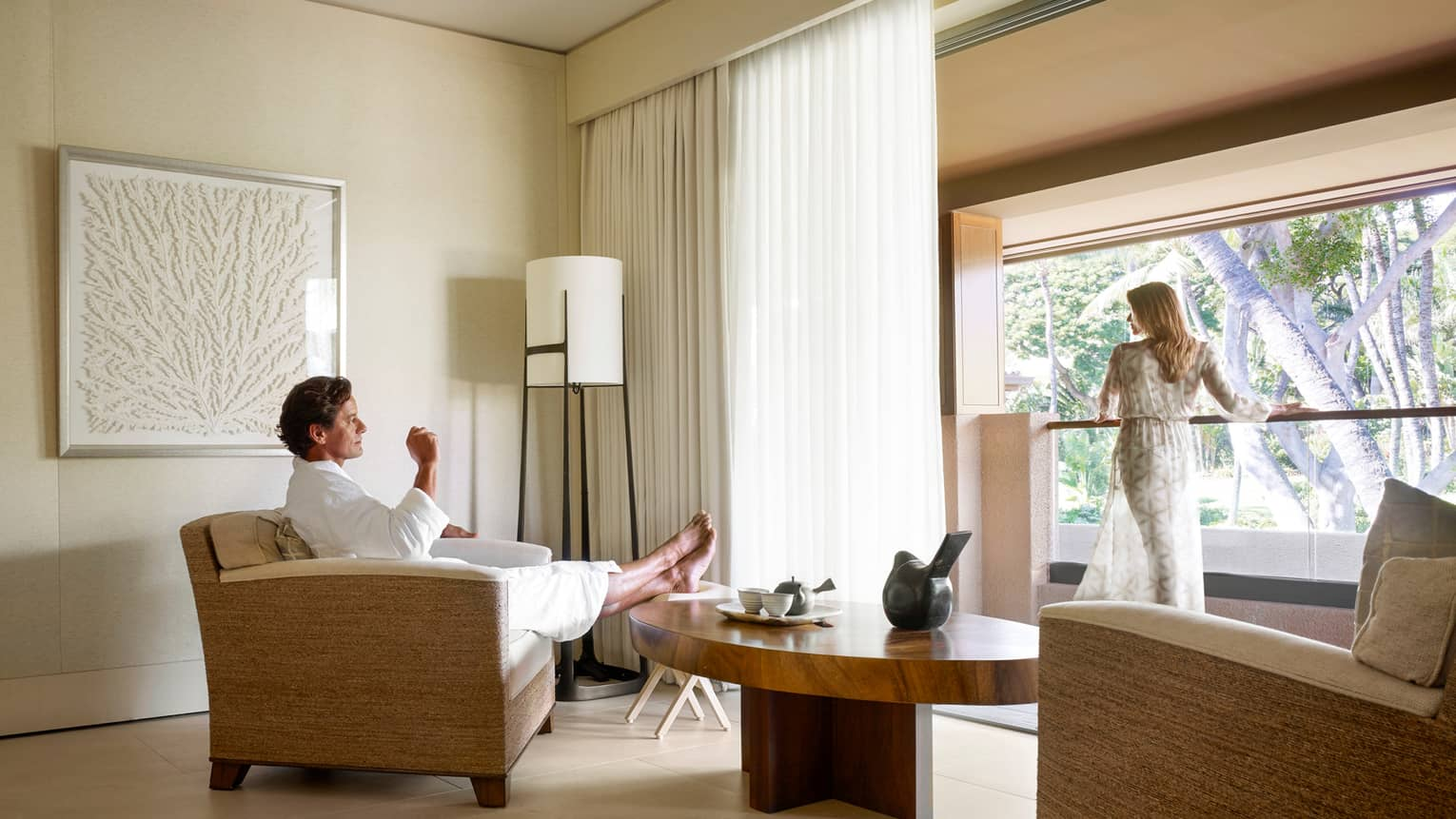 Man in white bathrobe kicks back in armchair in Spa room, woman in sheer robe stands at sunny window