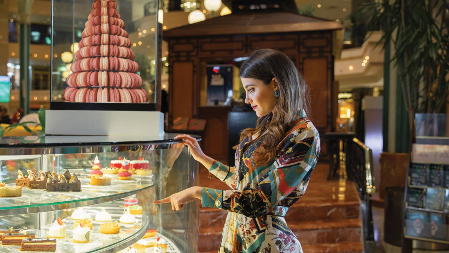A woman points to a pastry within a glass container of sweets at La Gourmandise