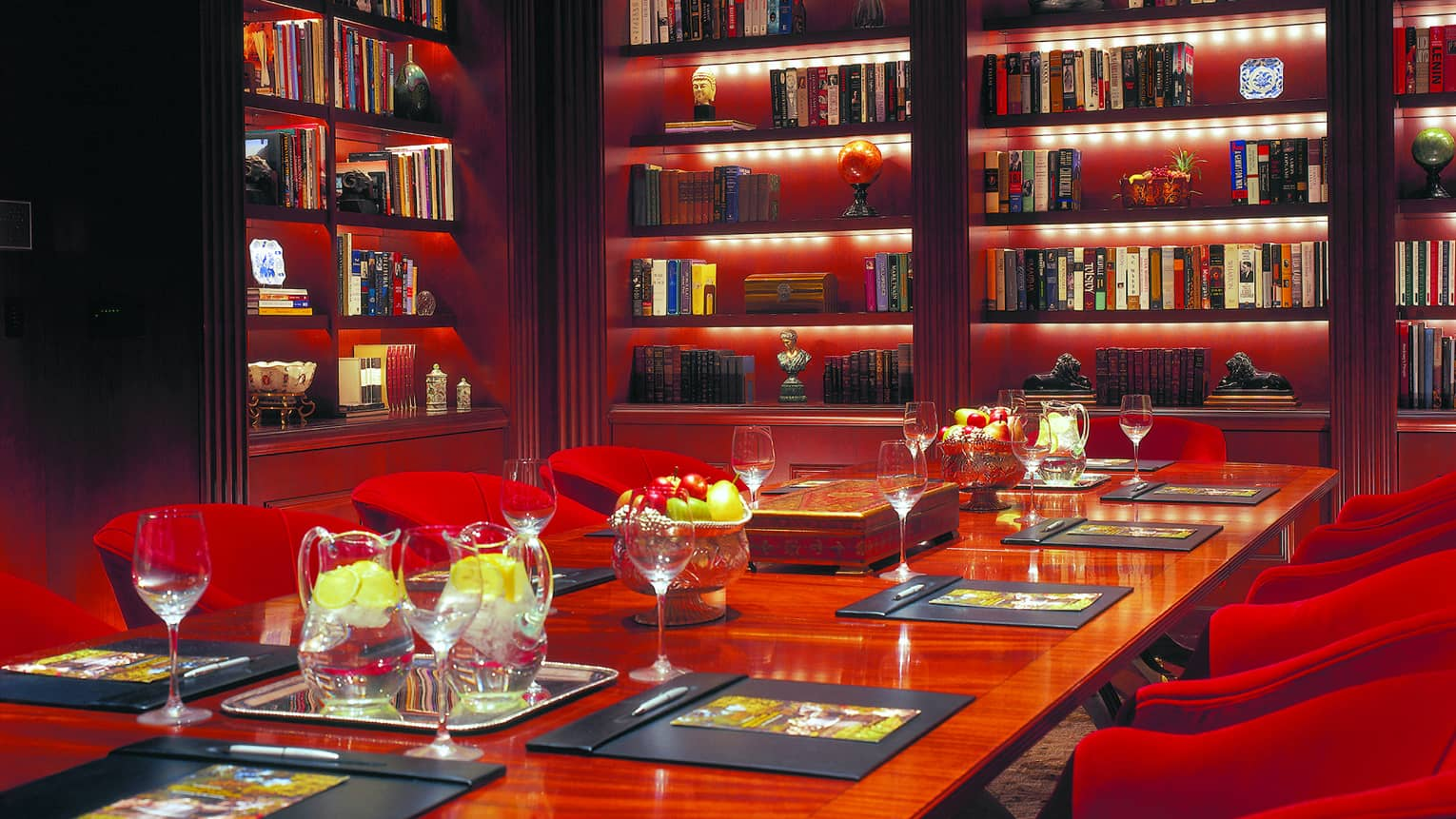 Sophisticated and intimate library with books on shelves, table with jugs of water, red lounge chairs