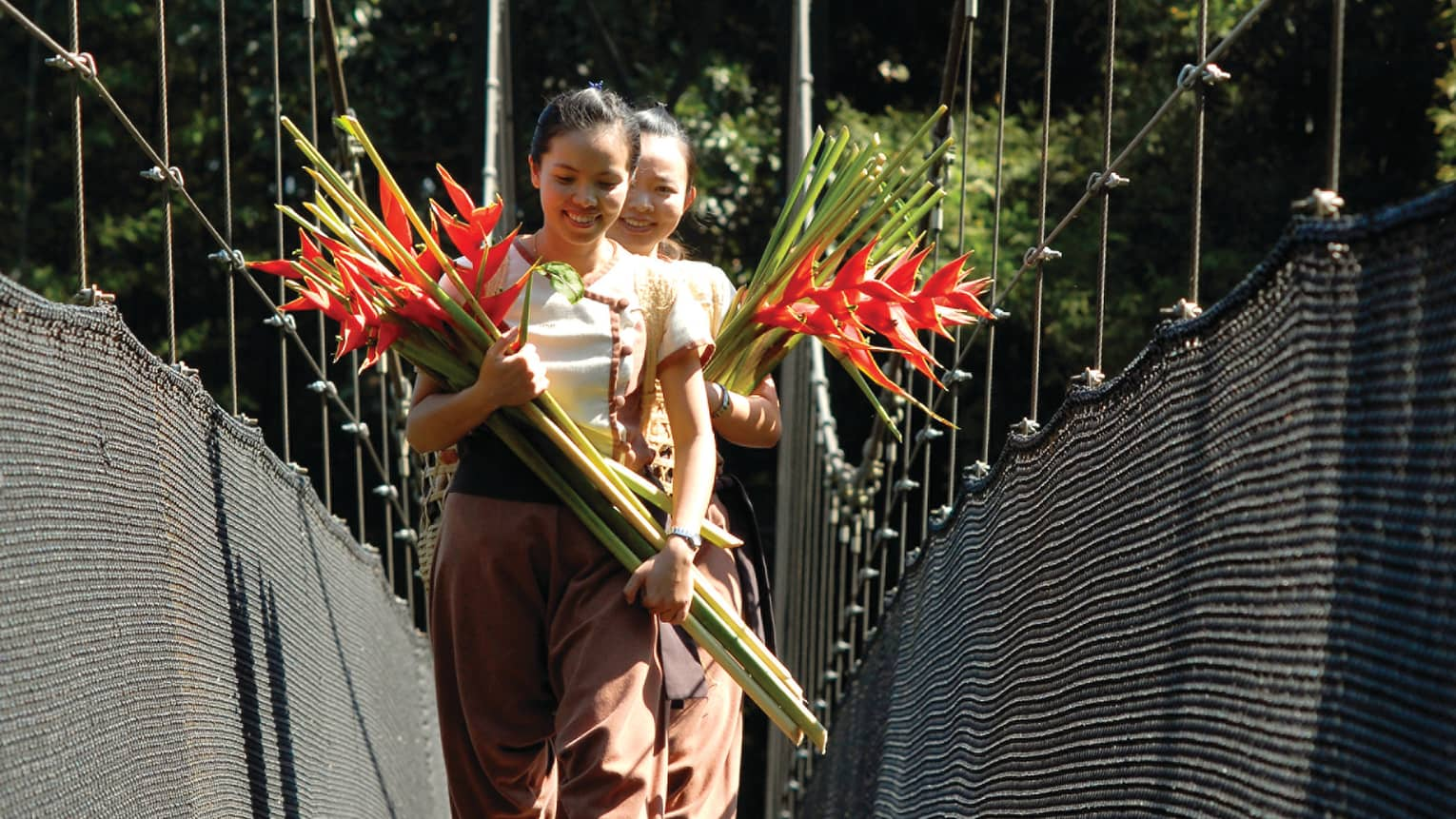 Two women walk down bridge holding bouquets of long-stemmed tropical flowers