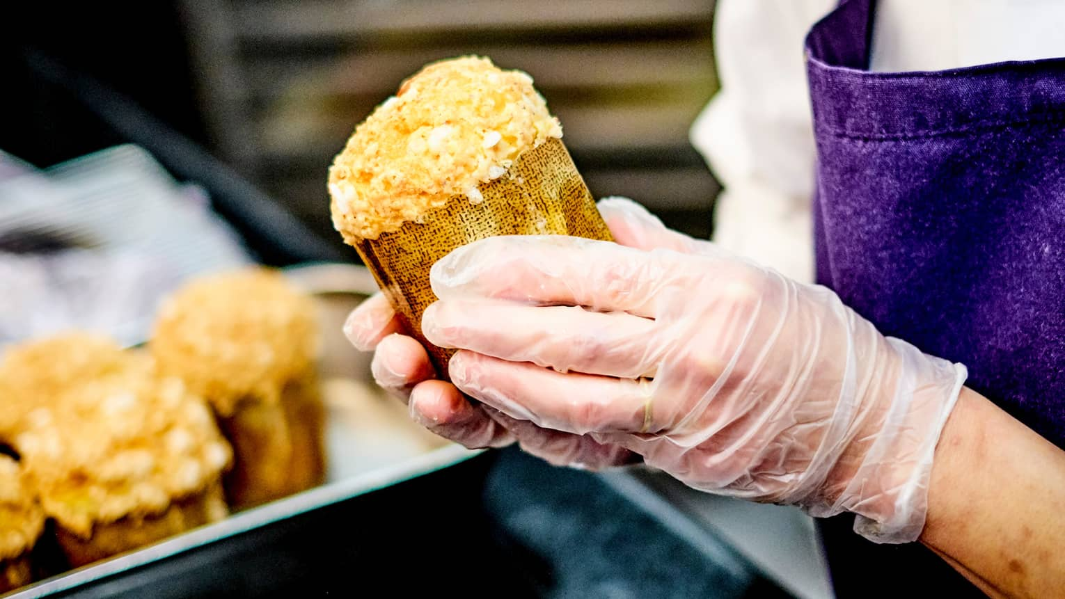 Close-up of chef pastry wearing gloves, holding rolled baked goods
