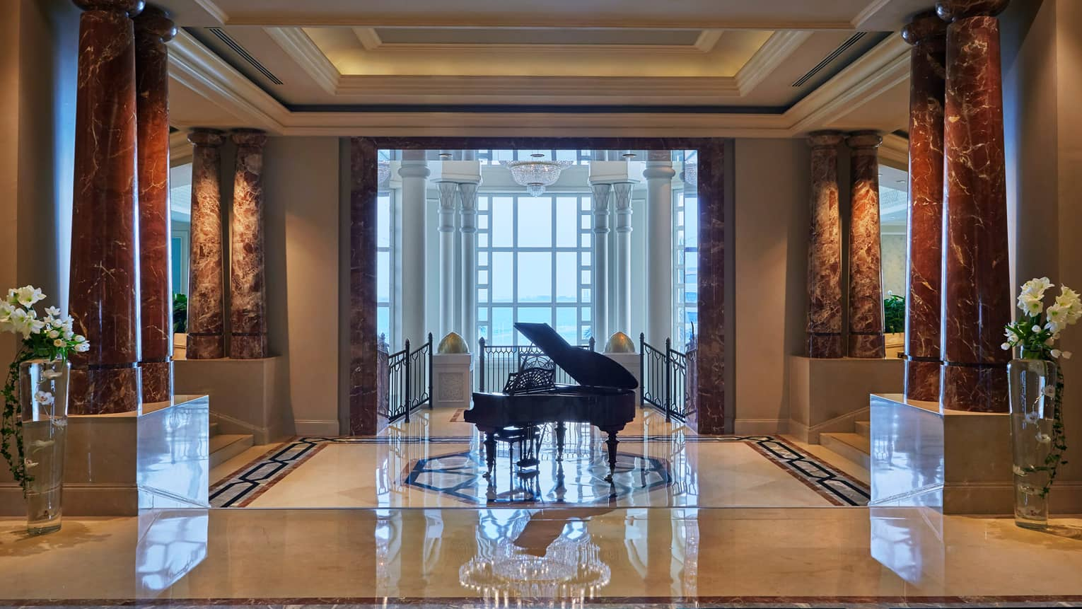 Grand piano by stairs in large lobby with marble floors