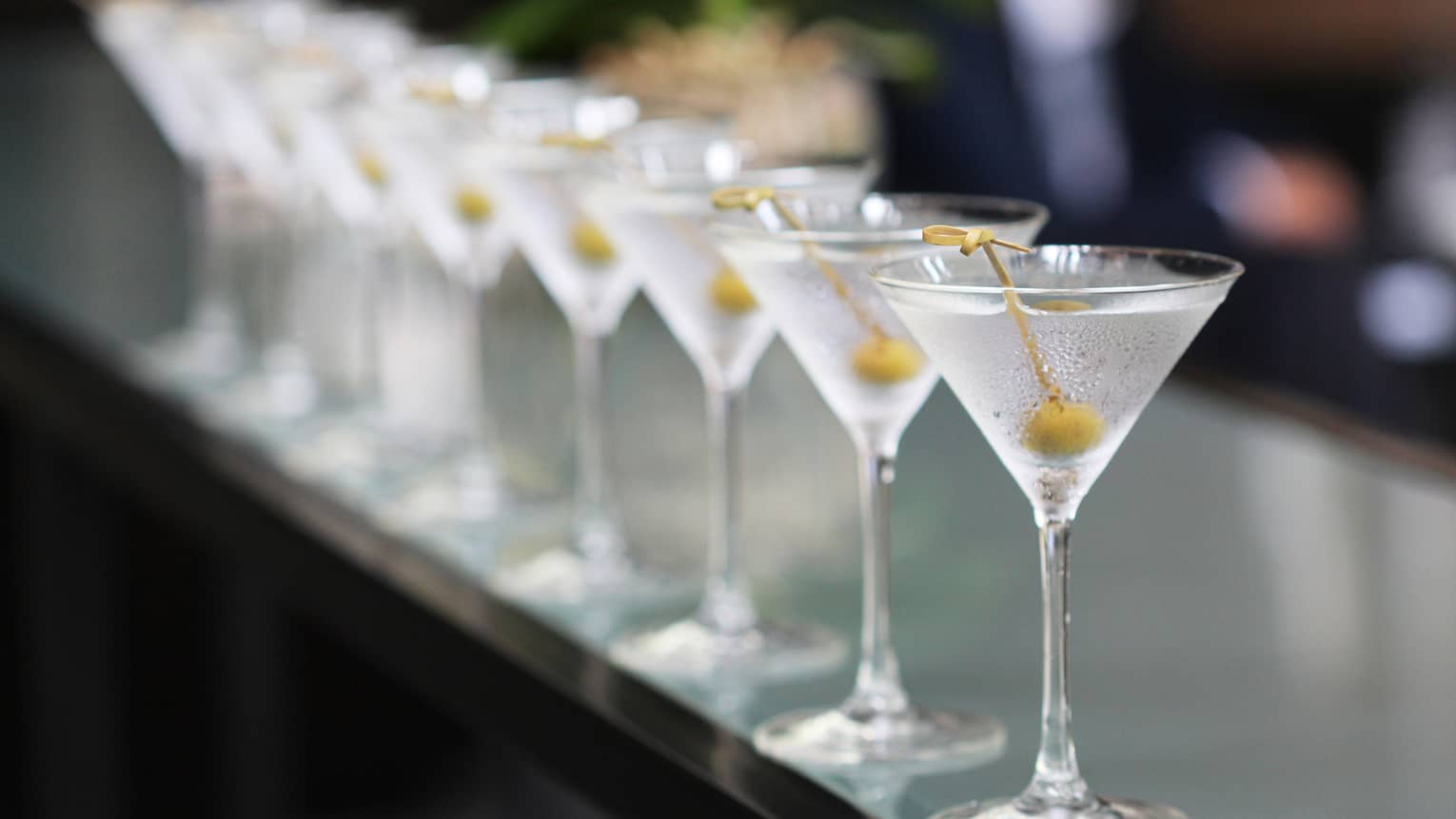 Row of tall martini glasses with green olives on toothpicks