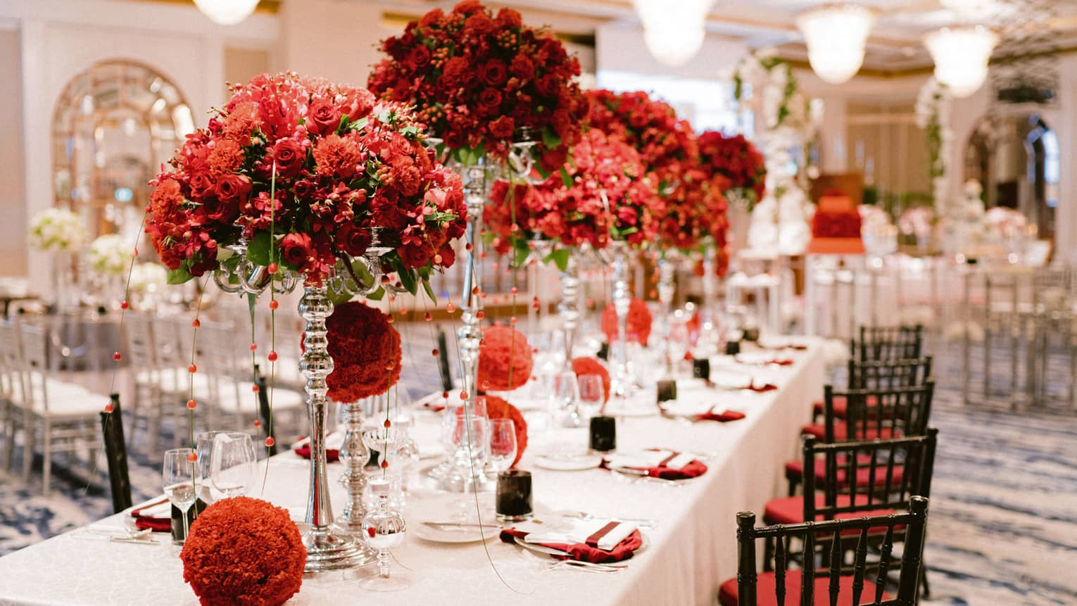 Red flower arrangements on dining table in wedding reception banquet room