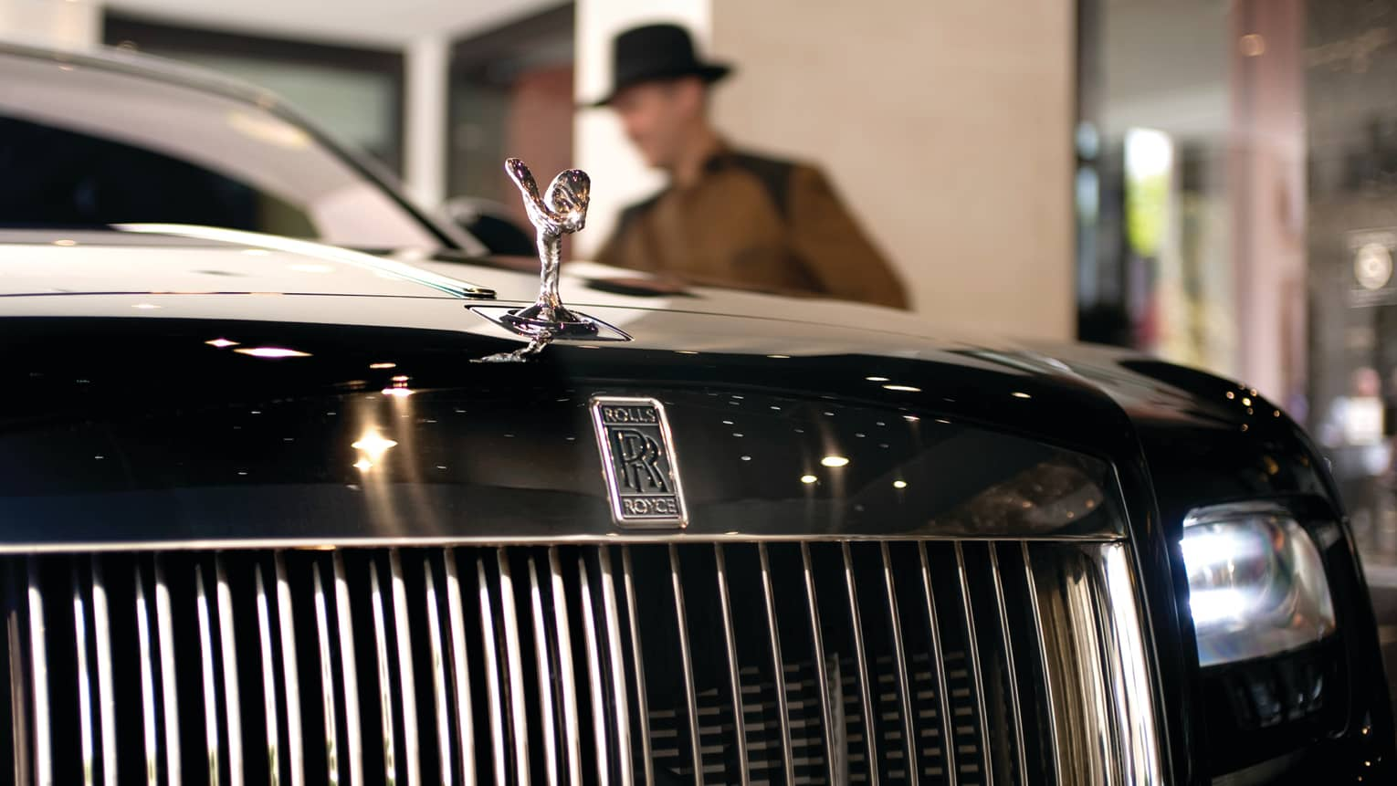 Close-up of Rolls Royce luxury car front grill, man in top hat in background