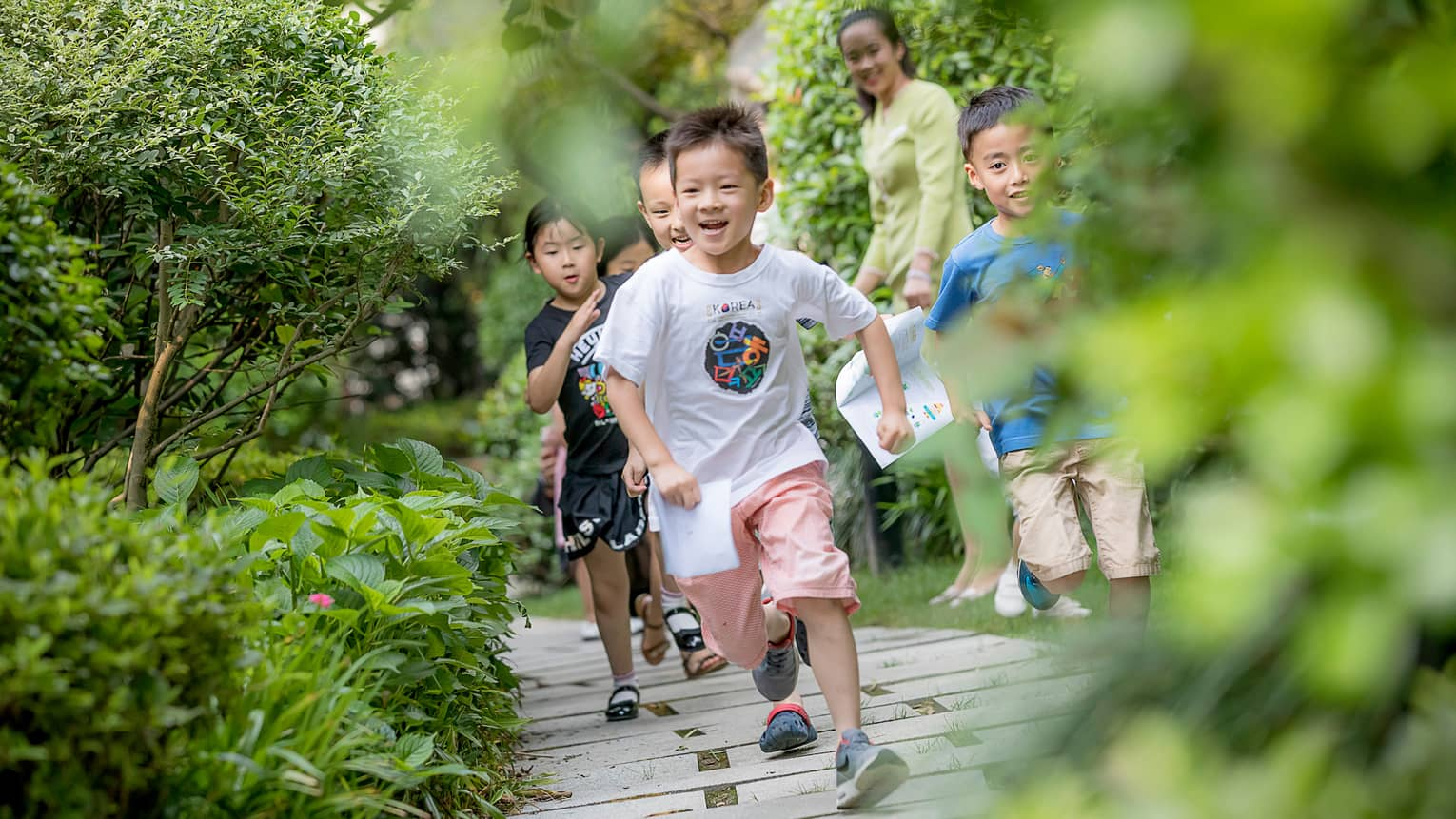 Smiling children run down wood path, bridge