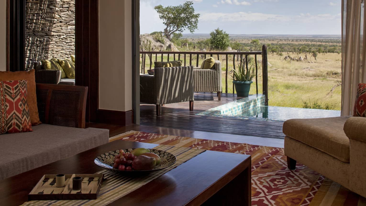 Terrace Suite coffee tables, sofas with colourful print accent pillows, open patio wall