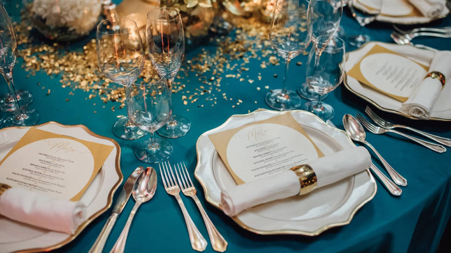 Elegant wedding banquet dining table, place settings with menus and gold accents