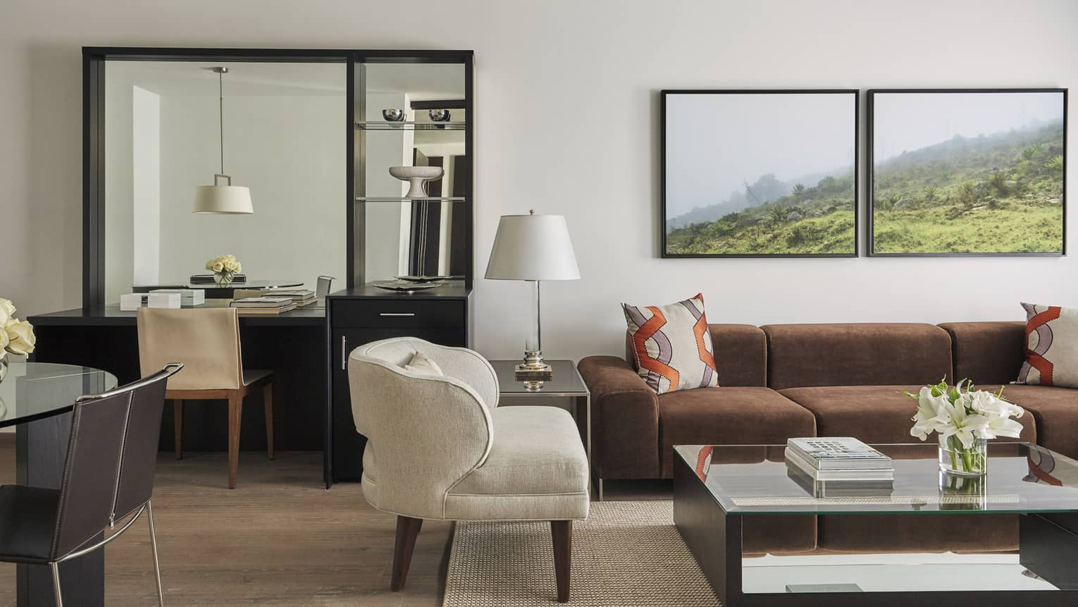 One-Bedroom Premier Suite living room with white armchair, brown sofa, tables and desk