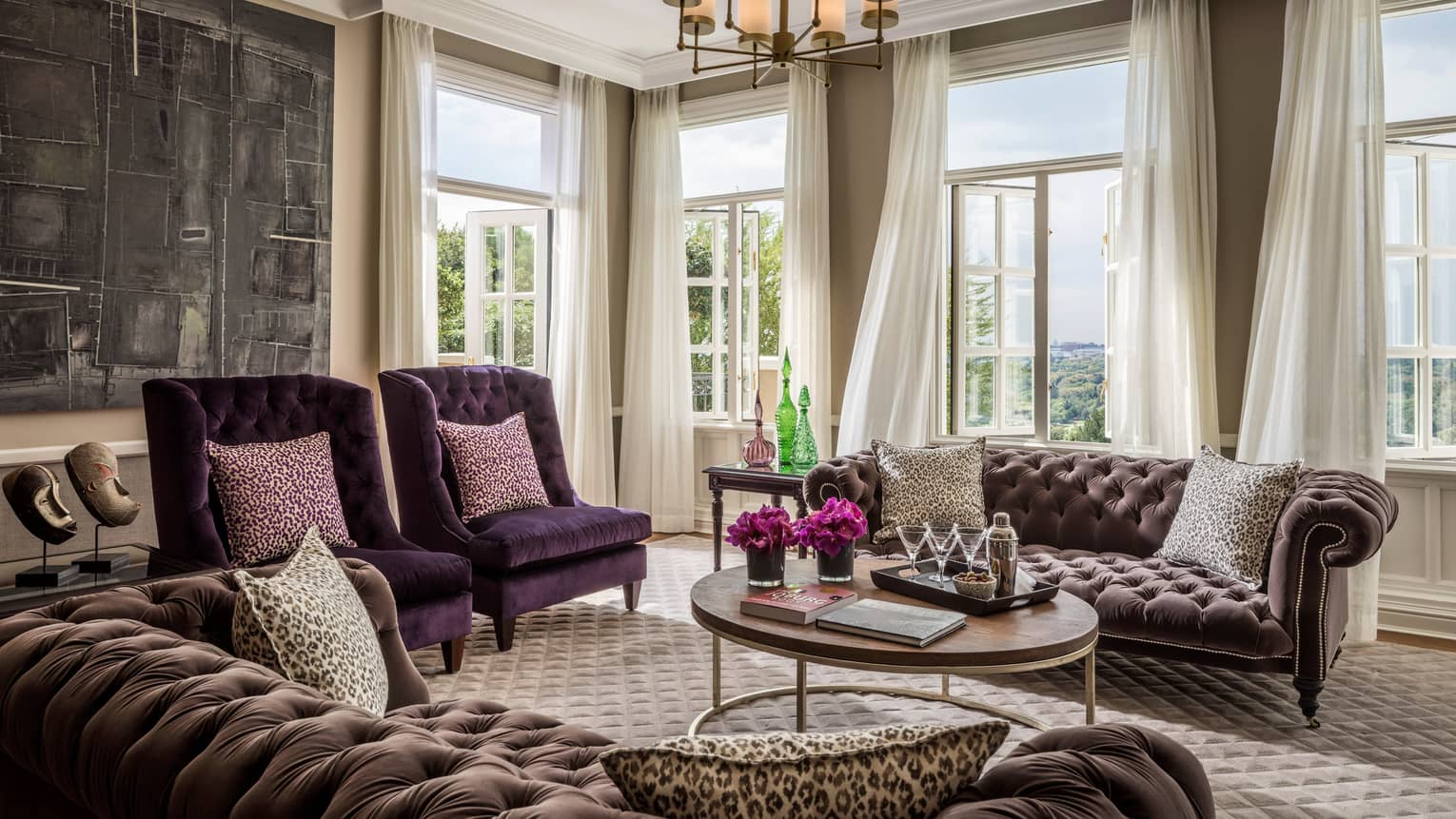 Presidential Suite tufted velvet sofas and armchairs around coffee table. sunny corner windows, curtains