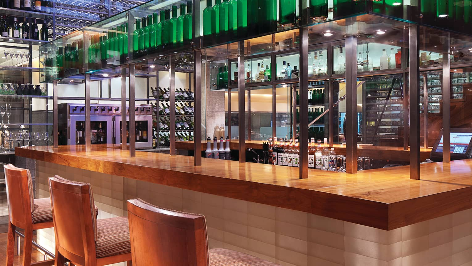 San Qi stools line modern wood bar with steel poles, shelves with wine bottles