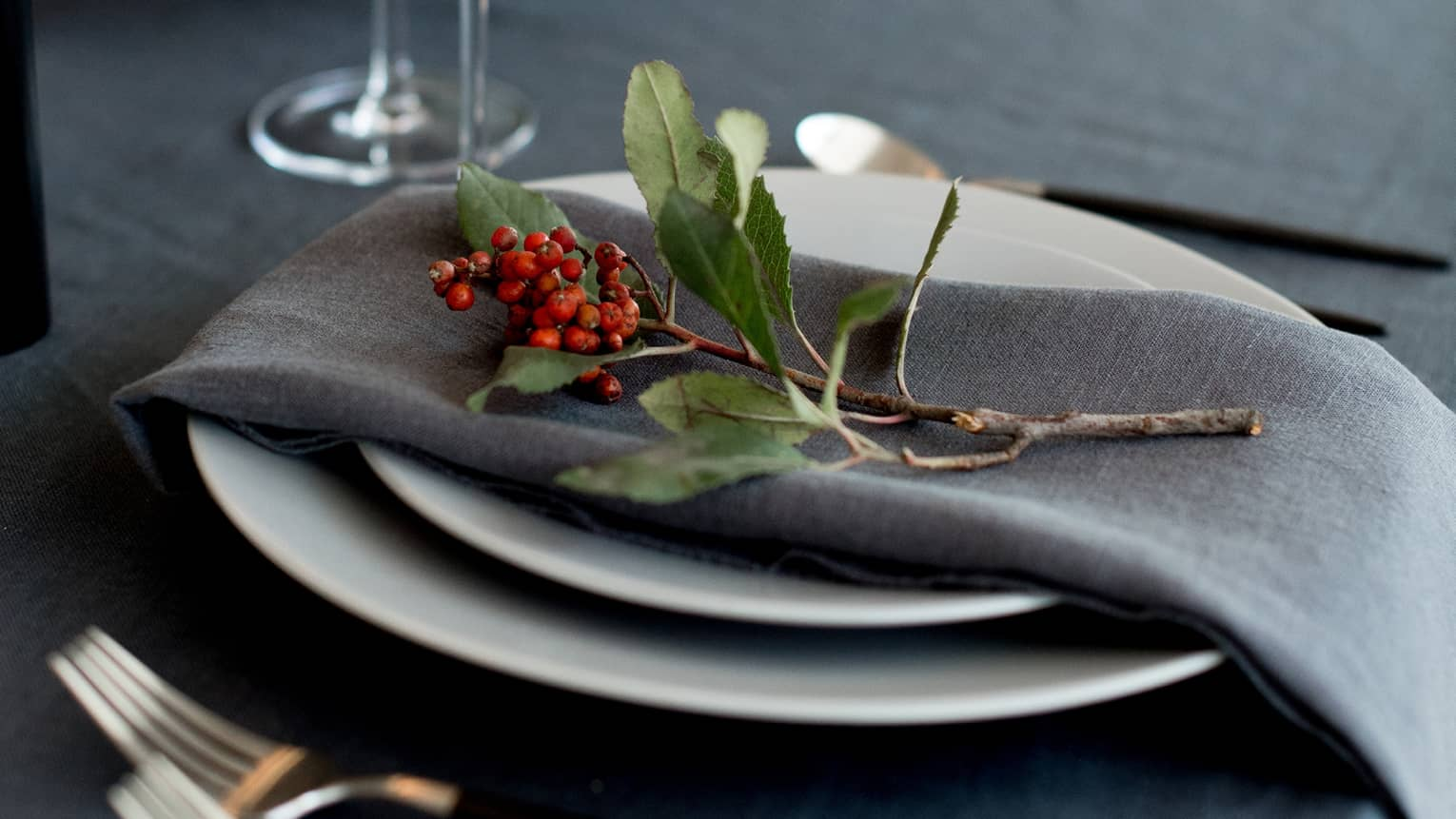 Table setting with white china topped with grey napkin and sprig of holly, cutlery, glasses
