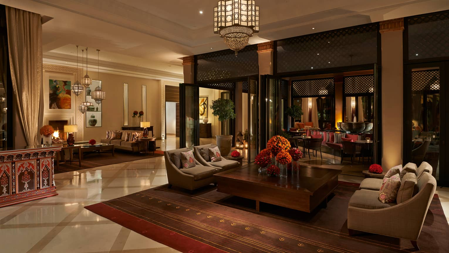 Dimly-lit hotel lobby with marble floors, seating area, rug under large Moroccan chandeliers