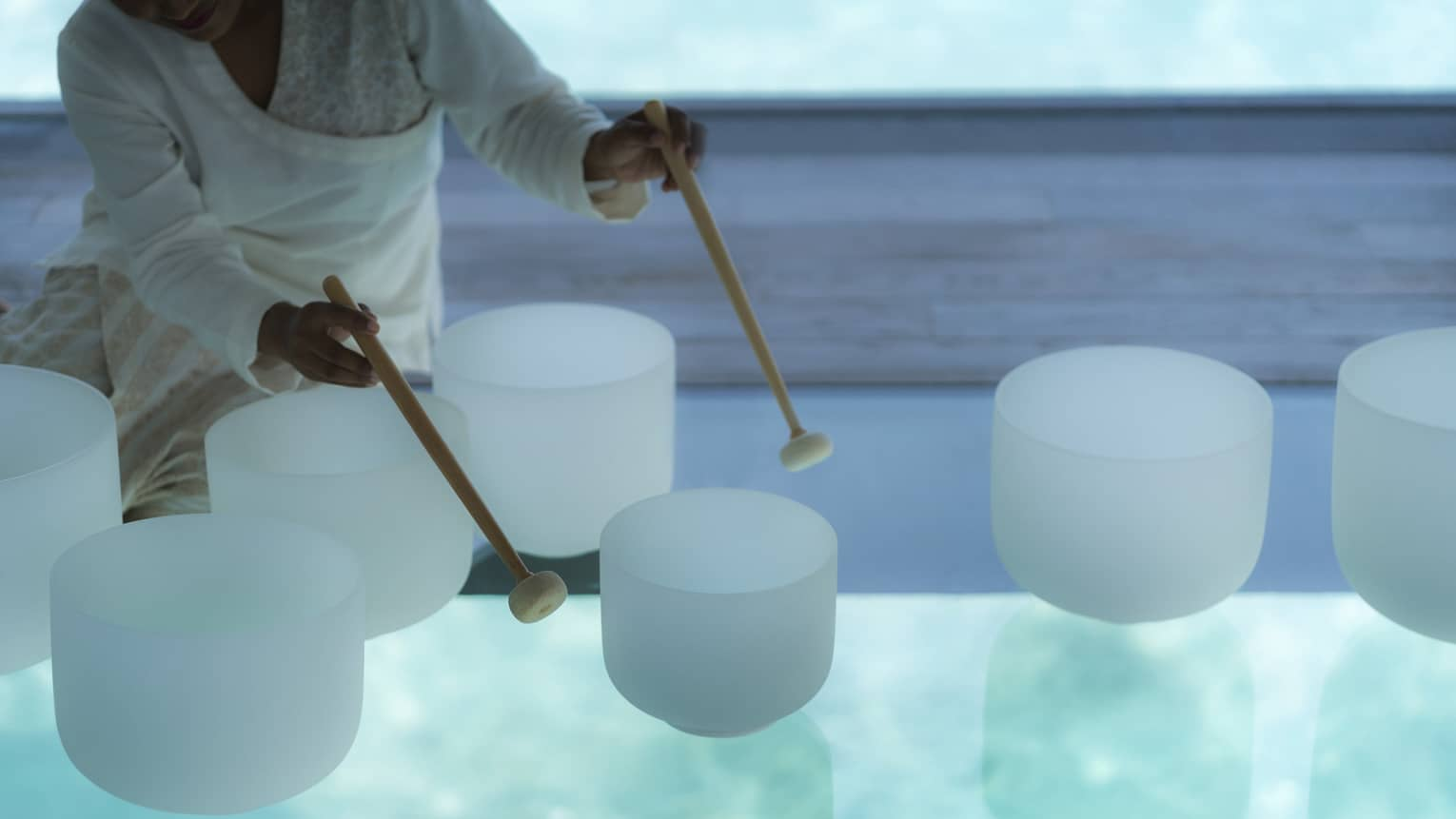 Spa staff plays various white crystal bowls with wood mallets during sound healing session