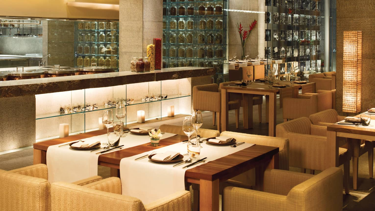 San Qi dining room, modern wood table with white runners, counter, glass wall with spices