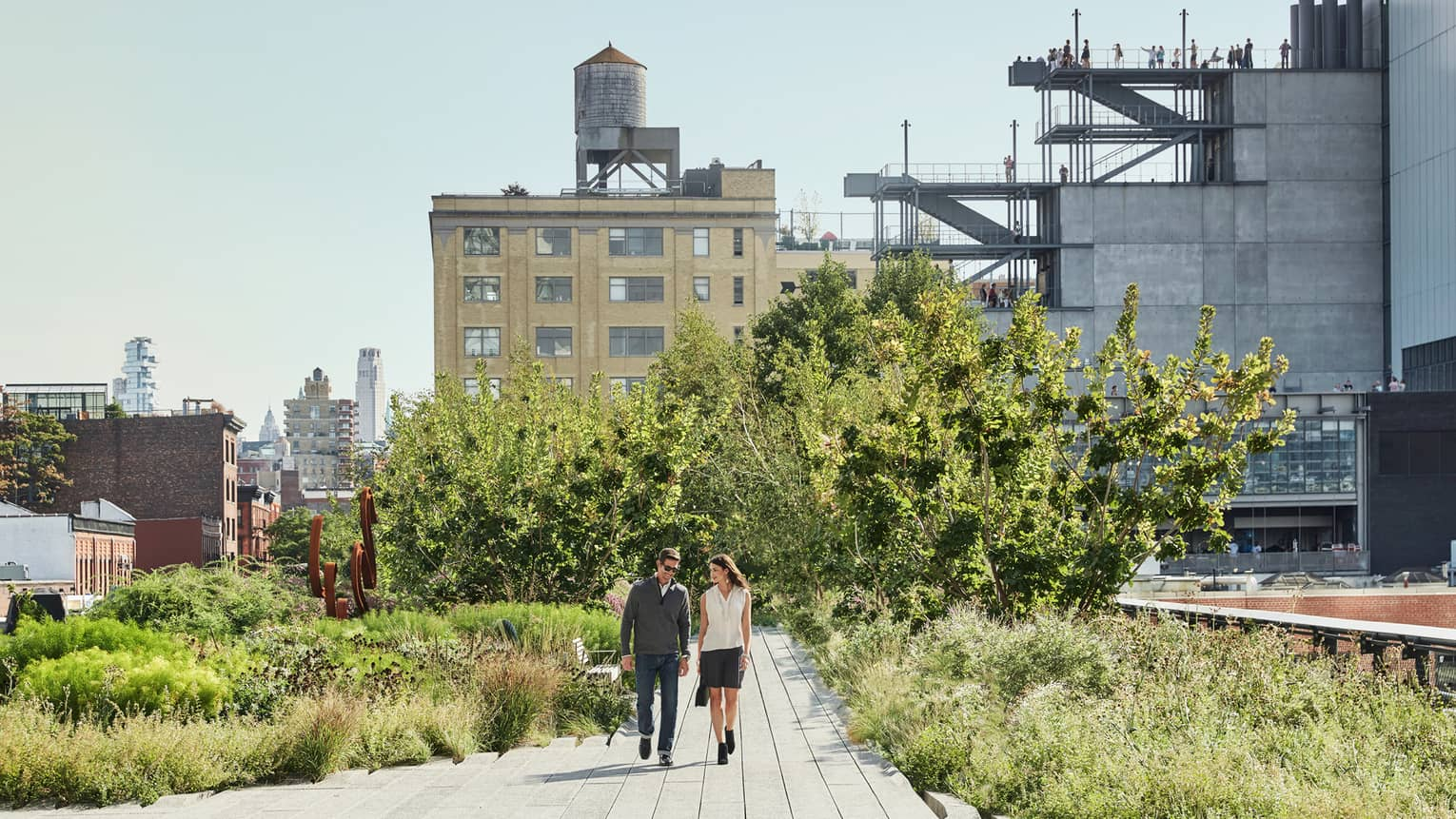 Couple walks along path surrounded by green trees, bushes on High Line on sunny day