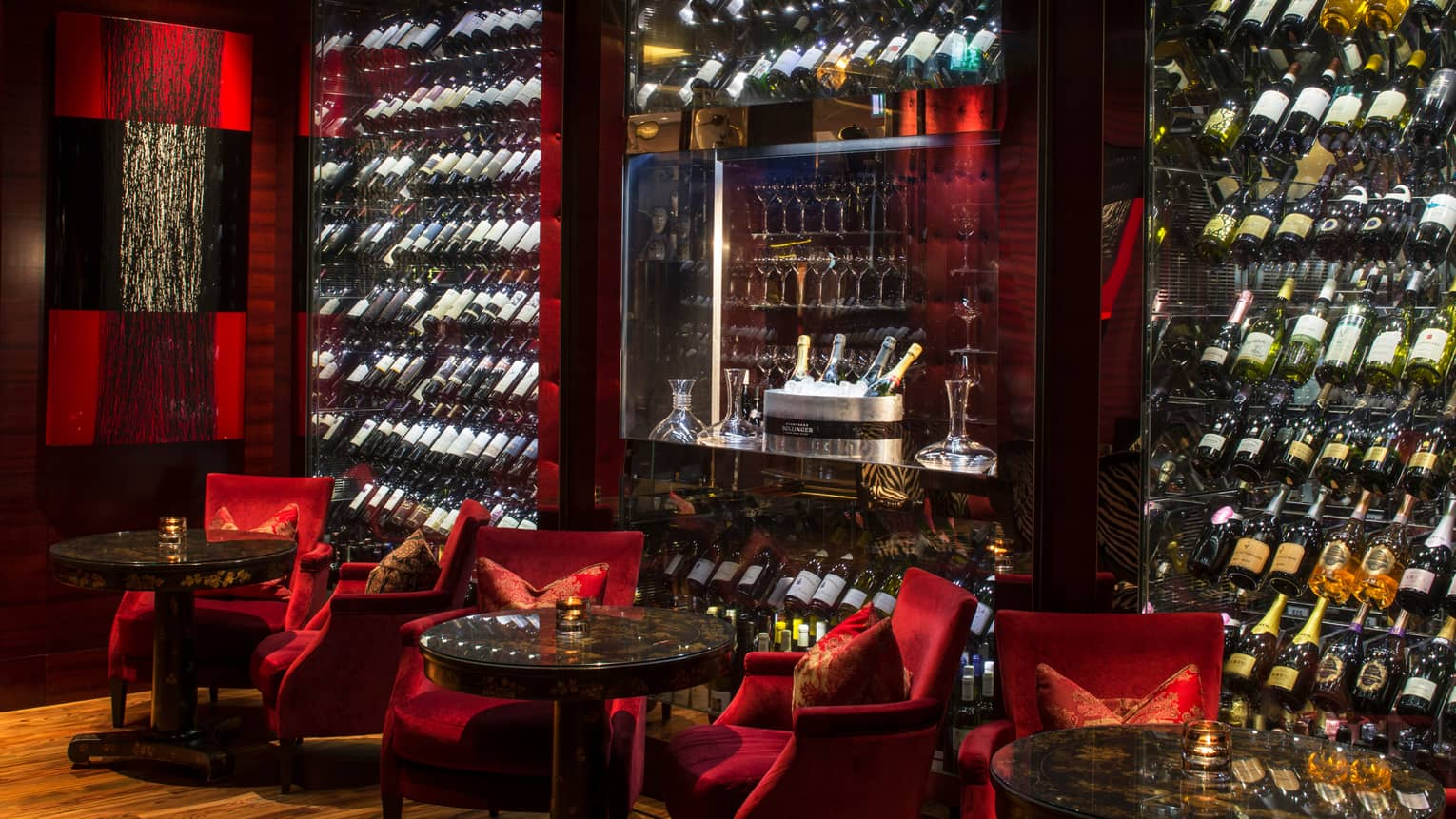 Amaranto Bar red velvet lounge chairs, large glass cellars with bottles, Champagne ice bucket