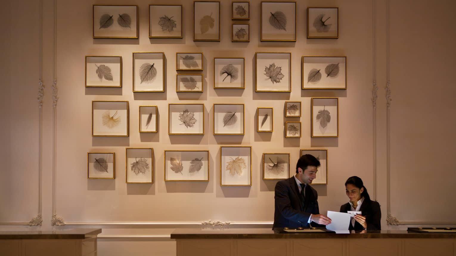 Two hotel staff look at paper at reception desk, tall wall with multiple framed leaf prints behind them