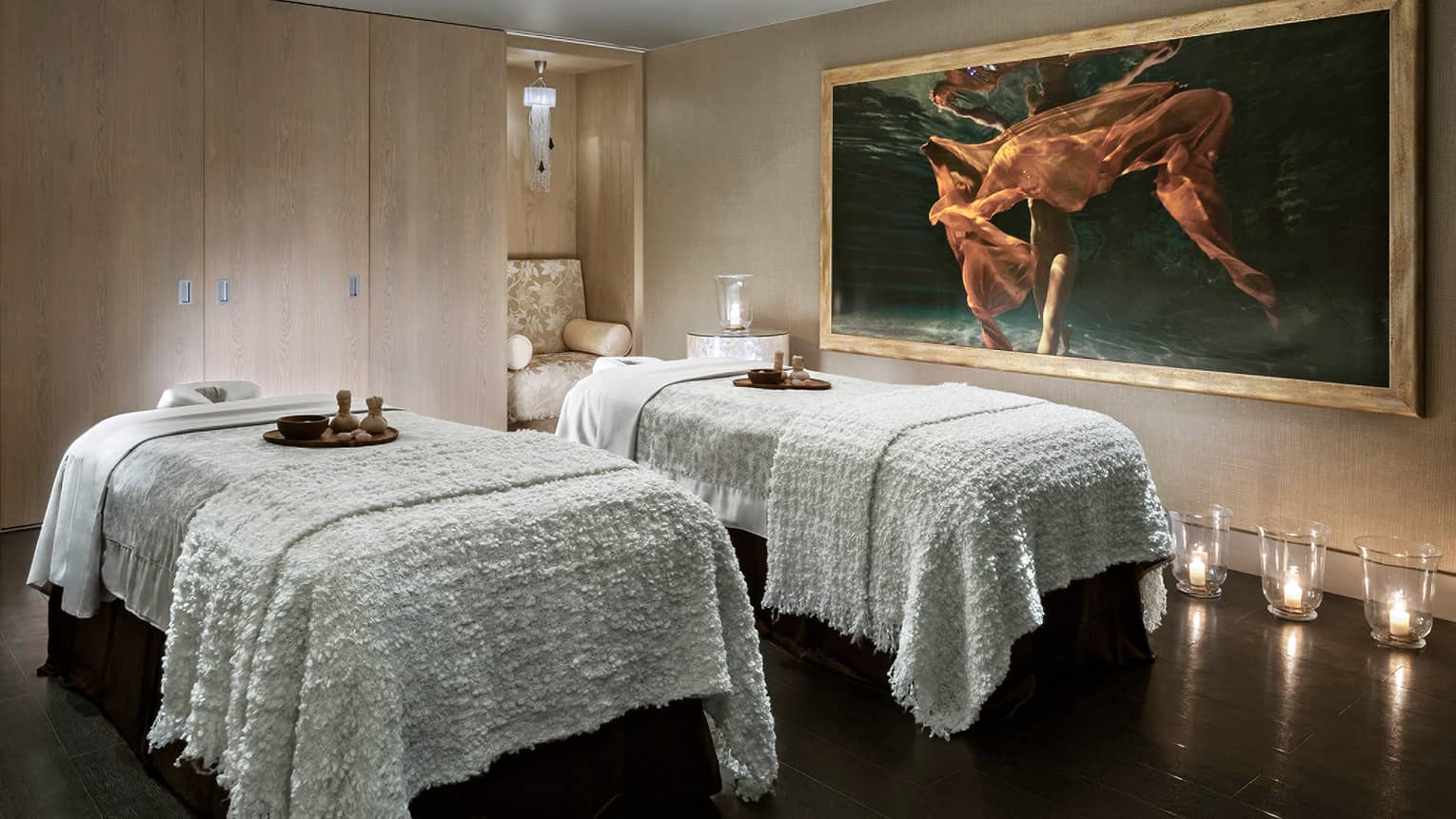 Couples spa beds with blankets in Alexandrite Massage Suite, glass candles on floor