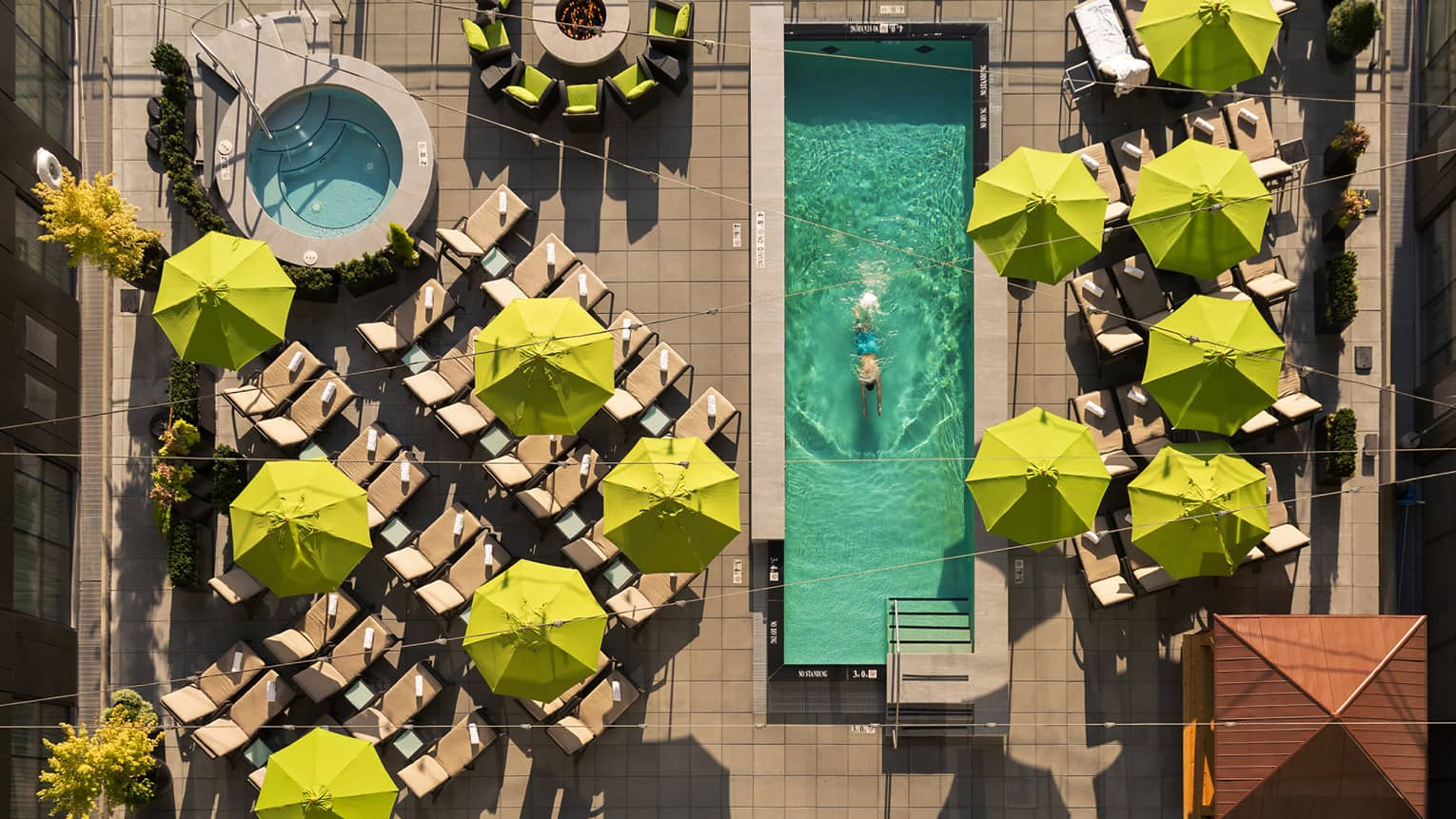 Aerial view of deck with yellow patio umbrellas, man swimming laps in long rectangular pool