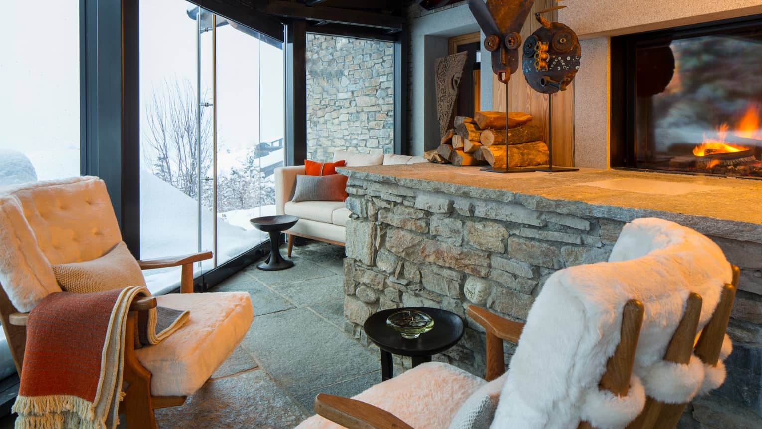 Cigar Room plush white lounge chairs by stone ledge with logs, sculptures, gas fireplace