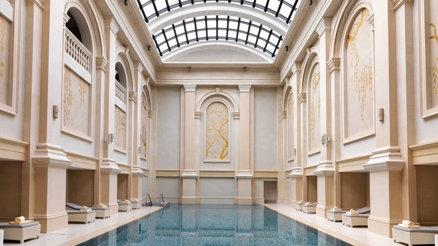Long blue indoor swimming pool lined with deck chairs, tall cream-coloured panelled walls leading to curved sunroof