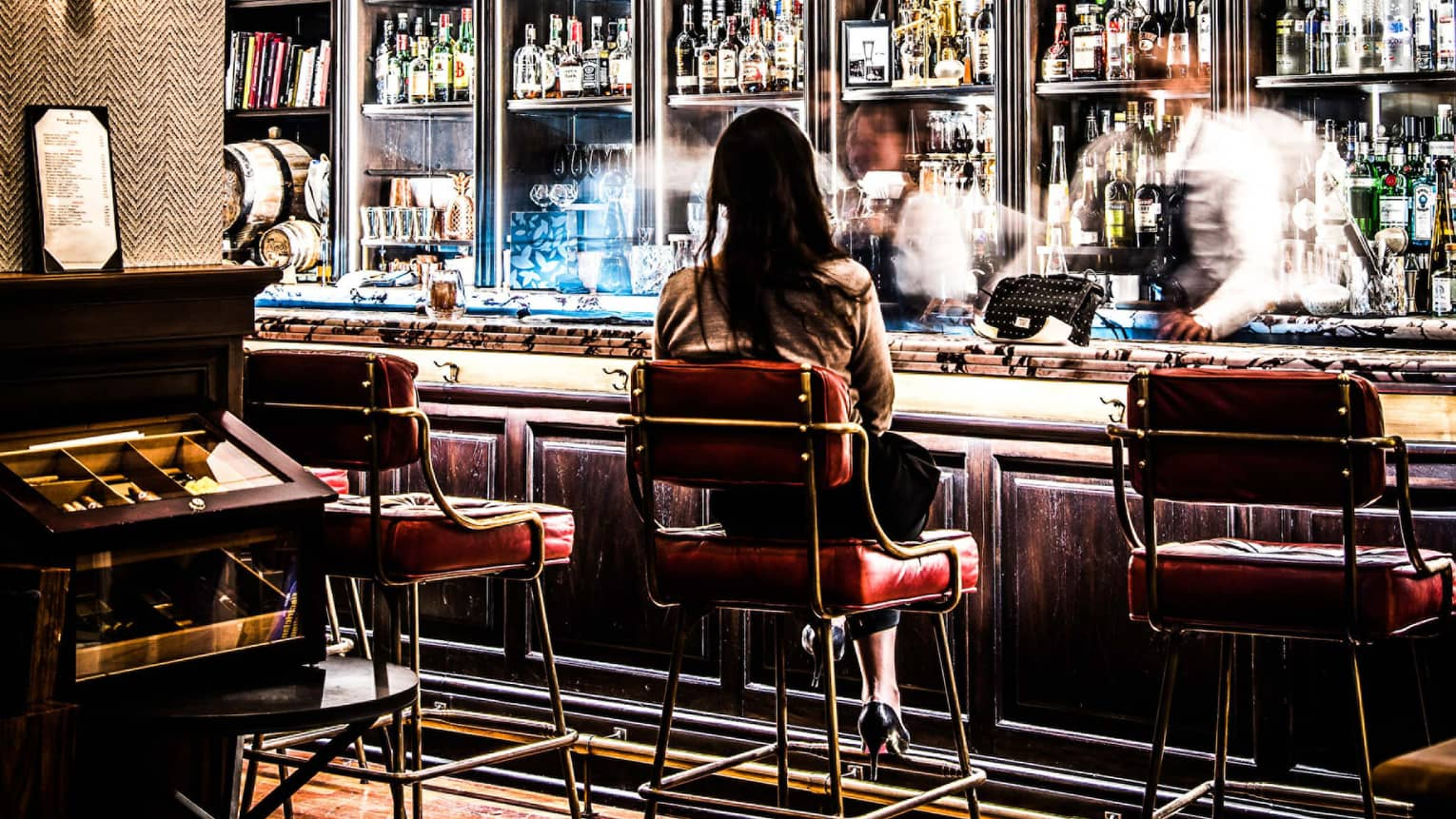 Woman sits on Fifty Mils plush red bar stool as mixologists work busily in front of liquor display