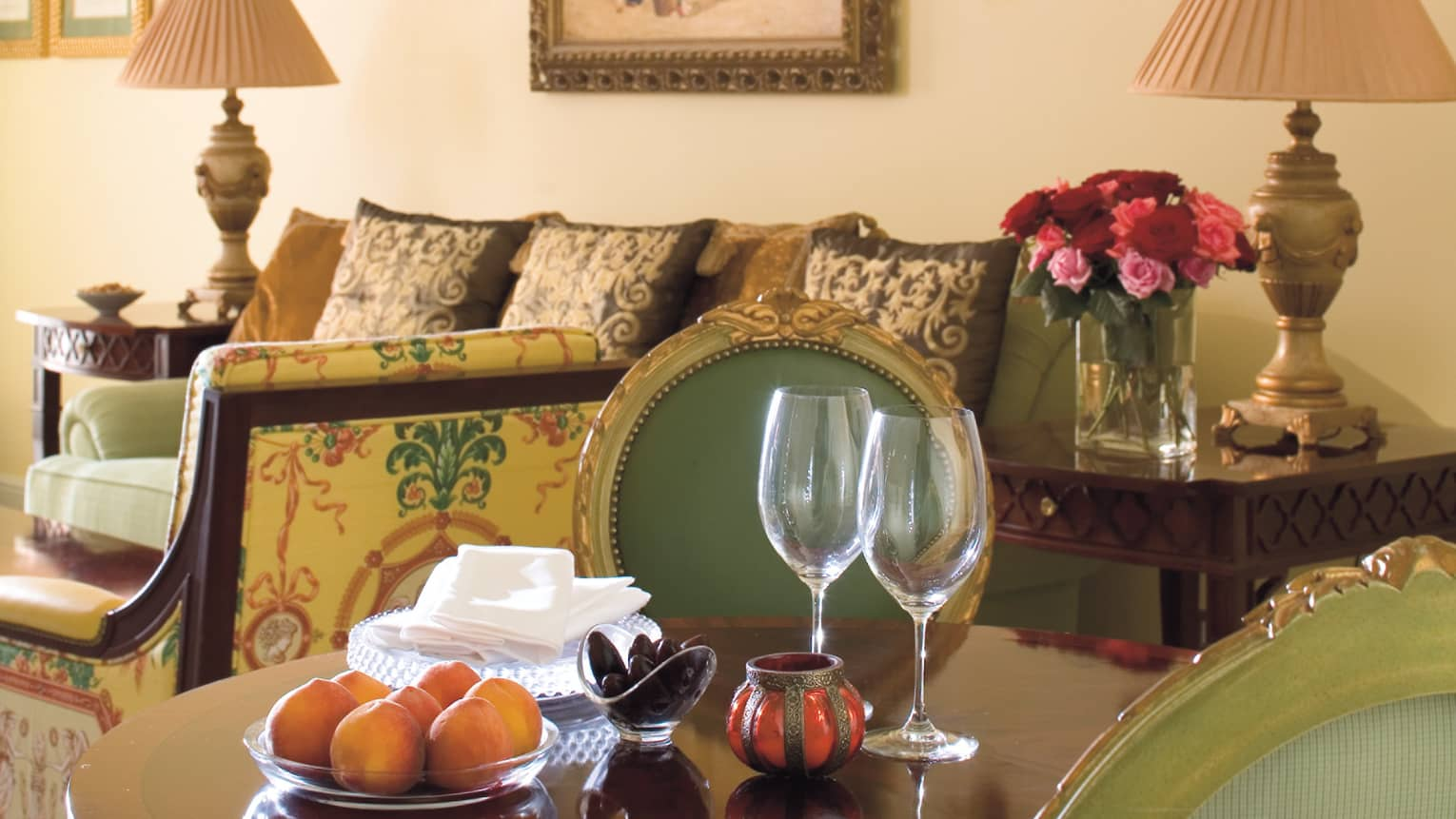 Close-up of wood dining table, wine glasses, bowl with oranges in Four Seasons Executive Suite
