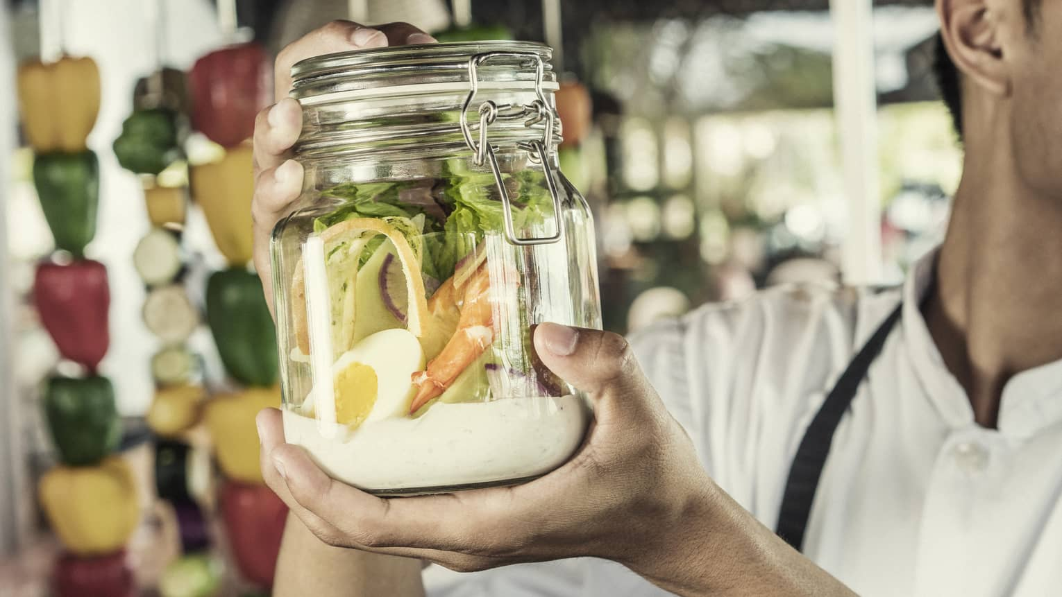 A chef shakes a caesar salad in a glass jar with some dressing