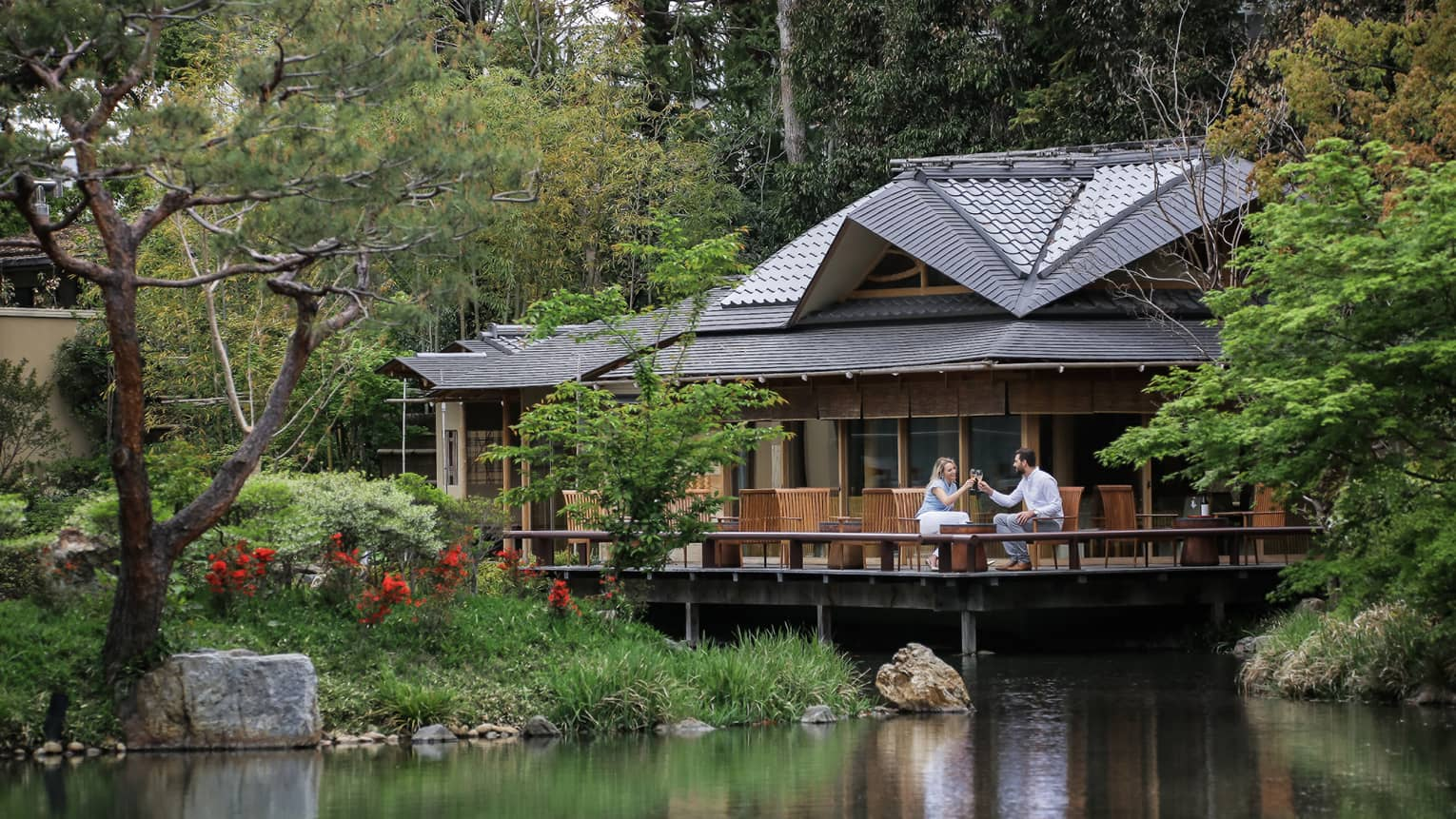 View across pond to restaurant patio where couple toasts with wine glasses