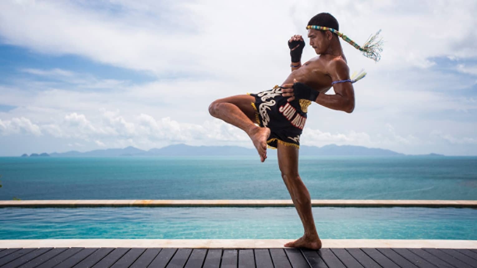 A guest practicing Muay Thai kickboxing by the ocean