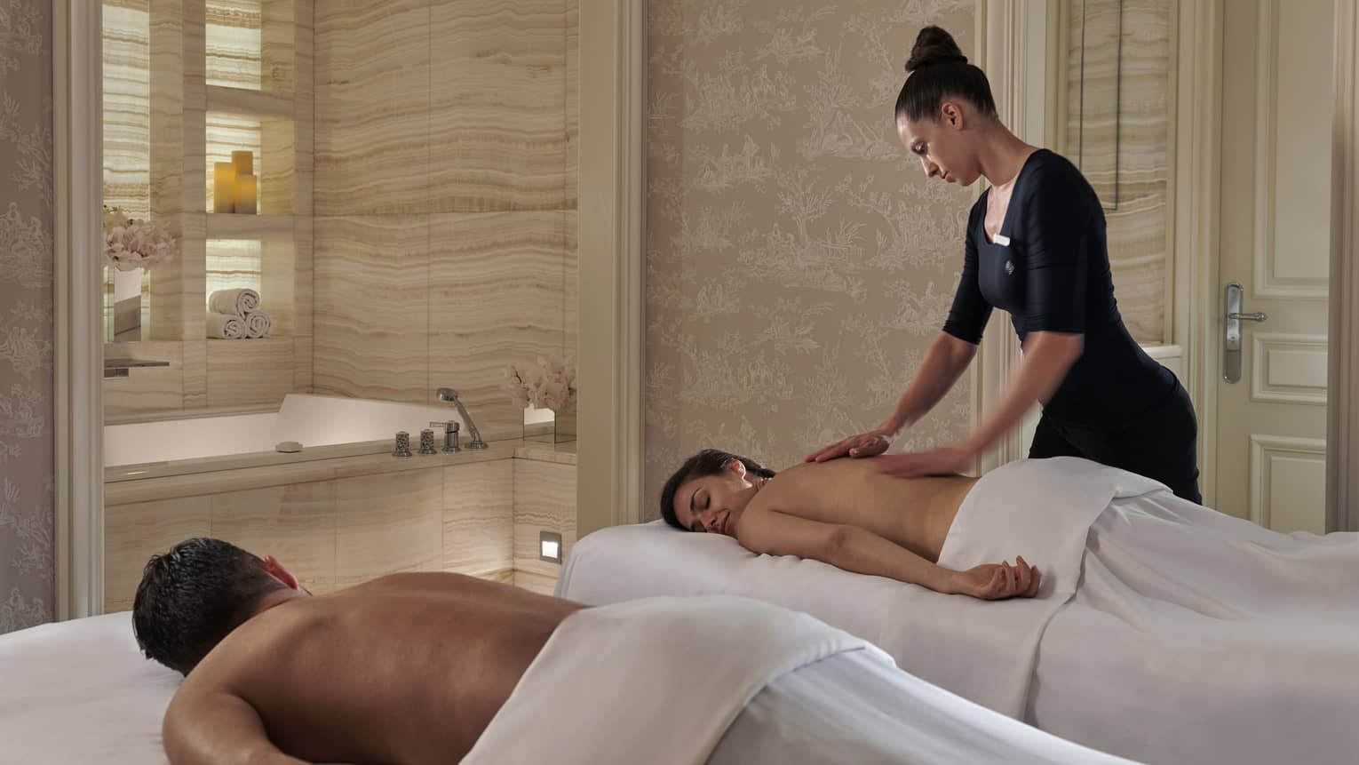 A four seasons staff massages a woman while her partner lies on a massage bet beside her at the four seasons george paris spa