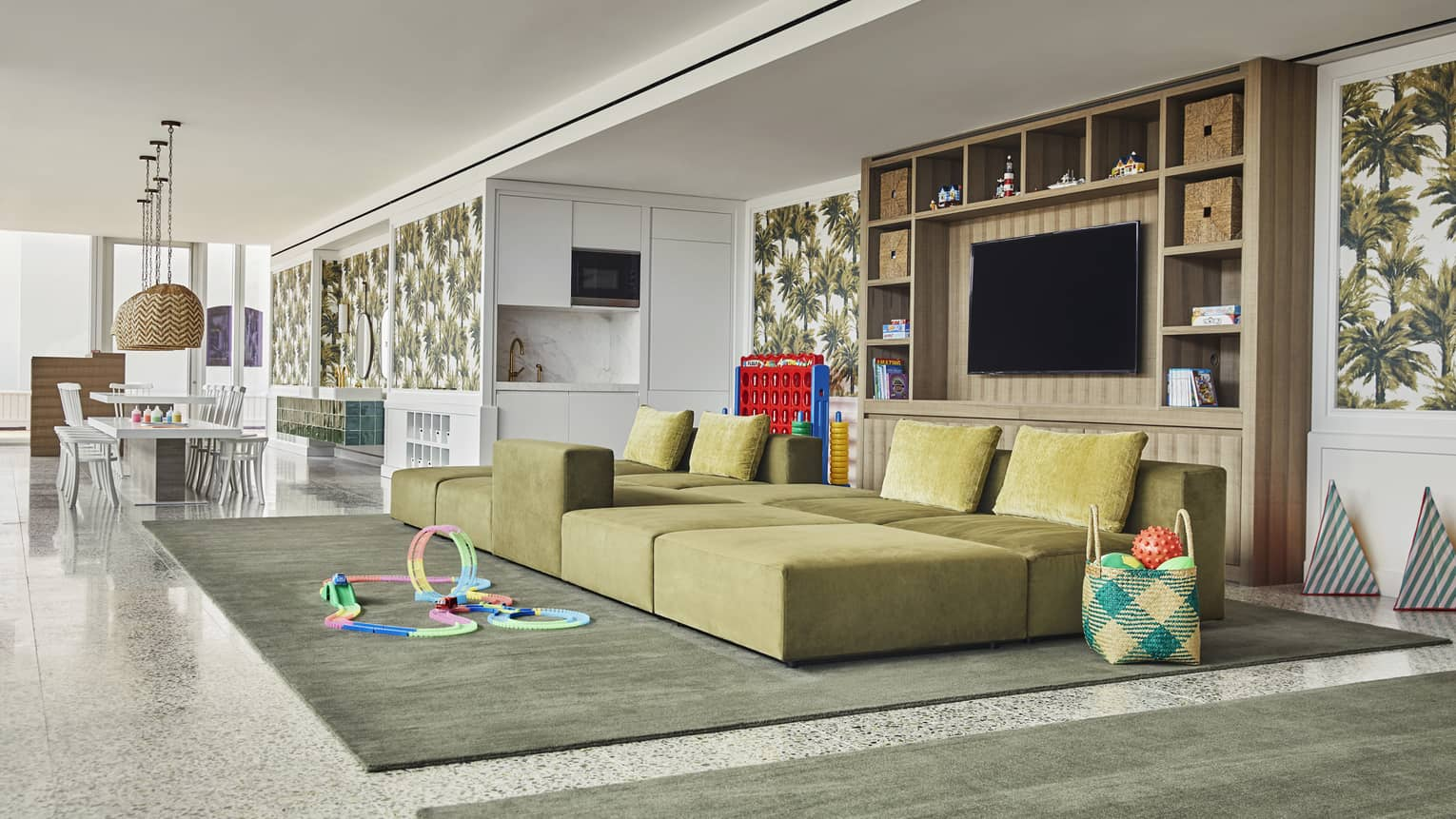 Bright kids facility with craft table, large sofa, toys and games. Specially-trained staff entertain children