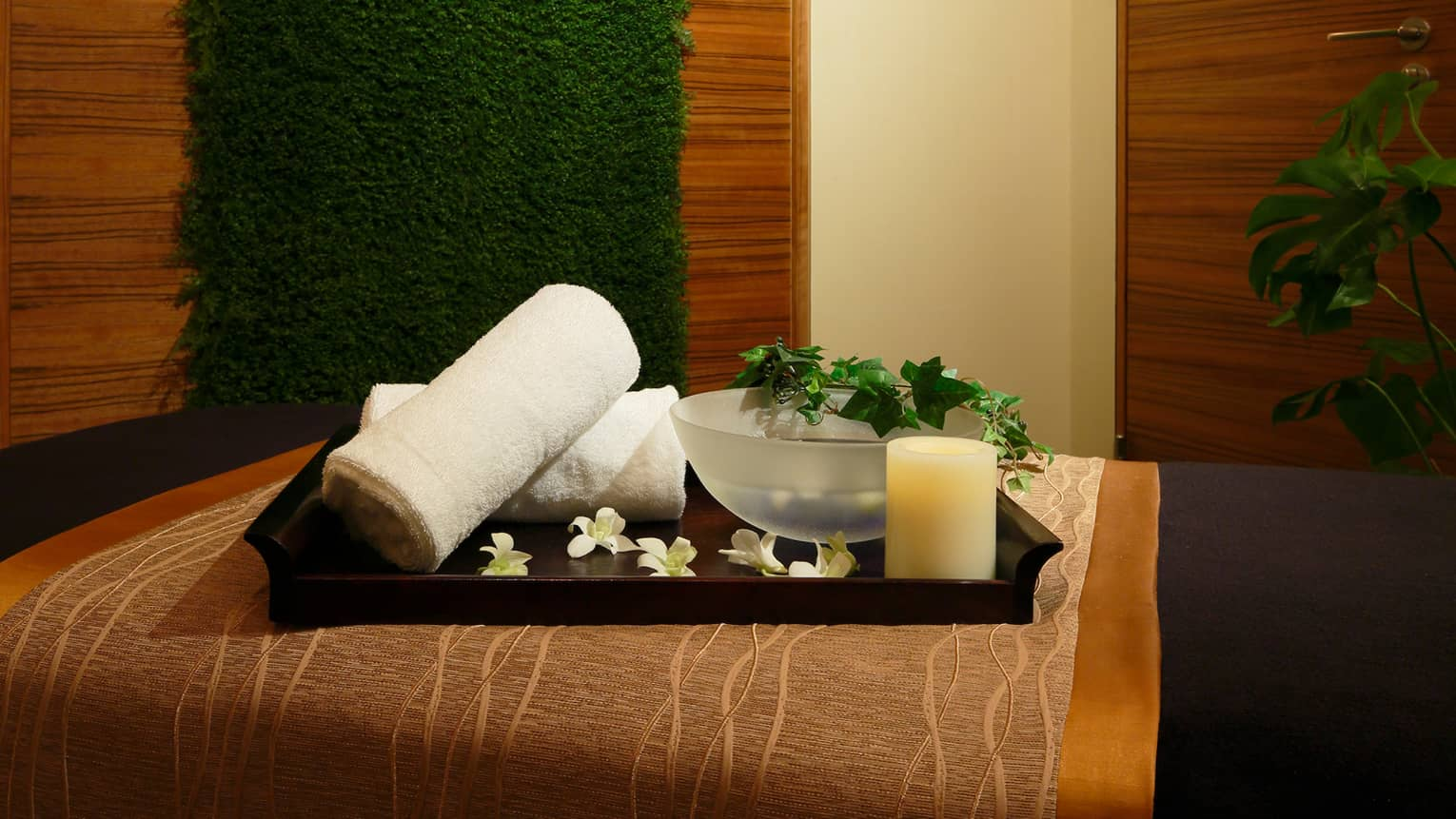 Wood tray with rolled white towels, flowers, candle, bowl with vine on spa bed