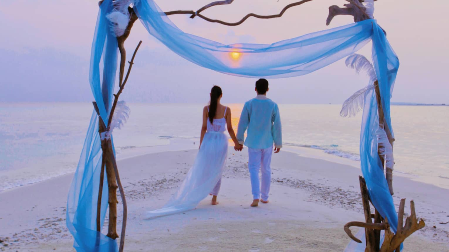 Wedding altar in front of couple walking on Blu Beach at sunset