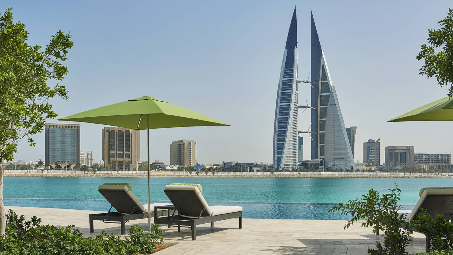 Two lounge chairs under lime-green umbrella on deck looking out at Arabian Gulf, modern tower